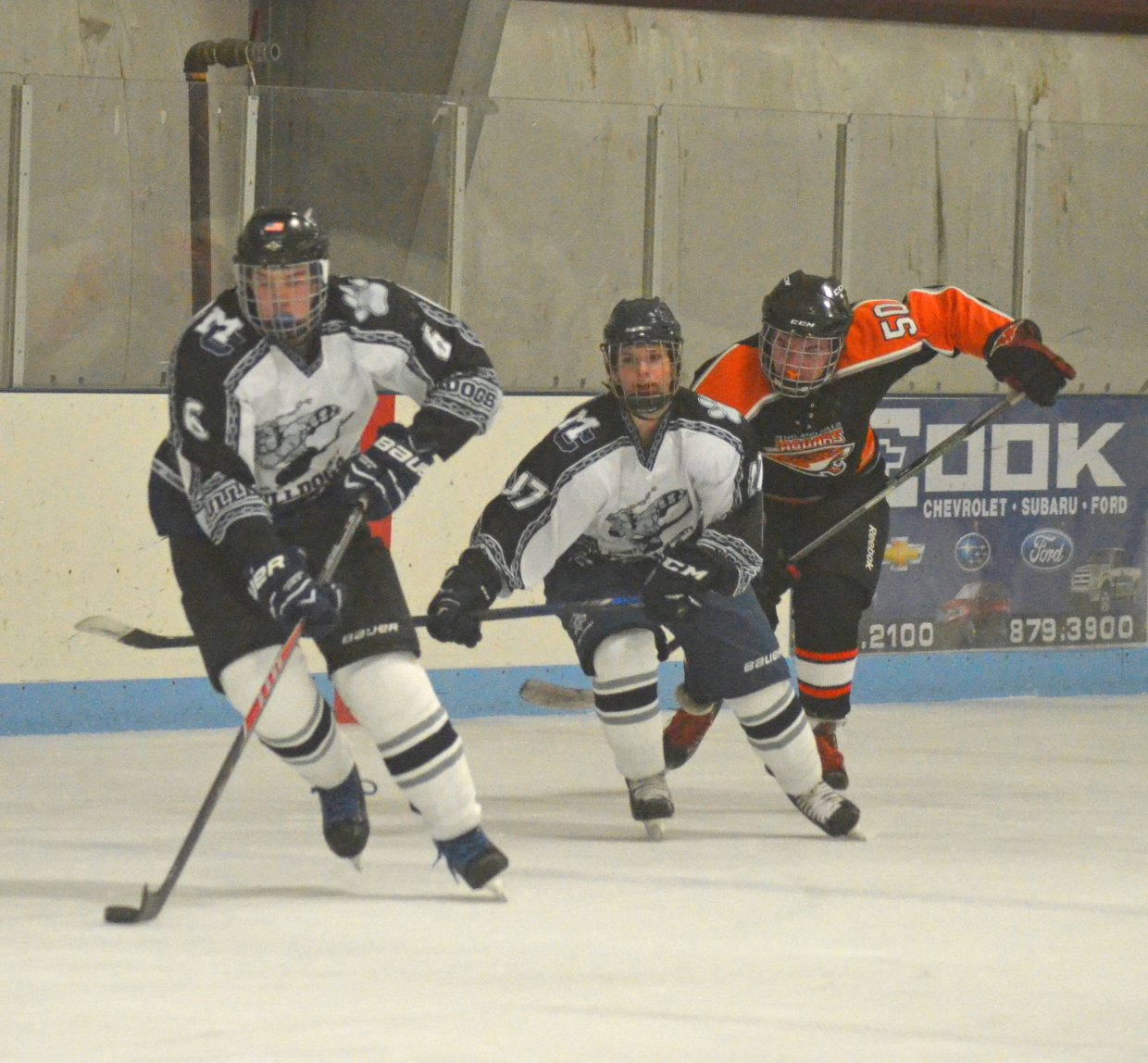 Brayden Tuttle (6) is on the approach to score, while teammate Kaitlyn Shrode (47) has his back in the Craig Youth Hockey Association 18U Midget team's game against the Hyland Hills Jaguars.