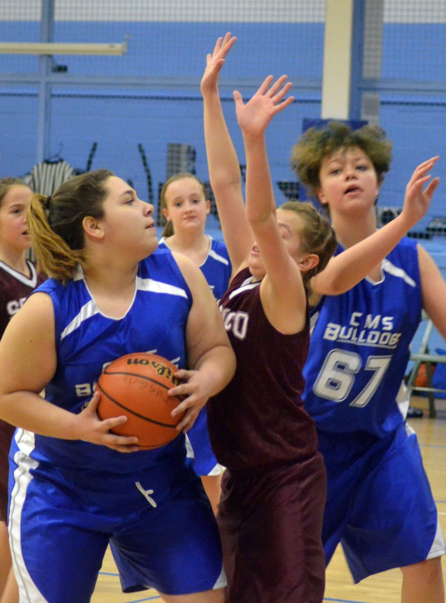 From left, Craig Middle School seventh-graders Tessona Gonzalez, Alayna Behrman and Stormy Townsend look to drive up the score for the seventh-grade B-Team's Thursday home game with Soroco. The Bulldogs won, 19-15.