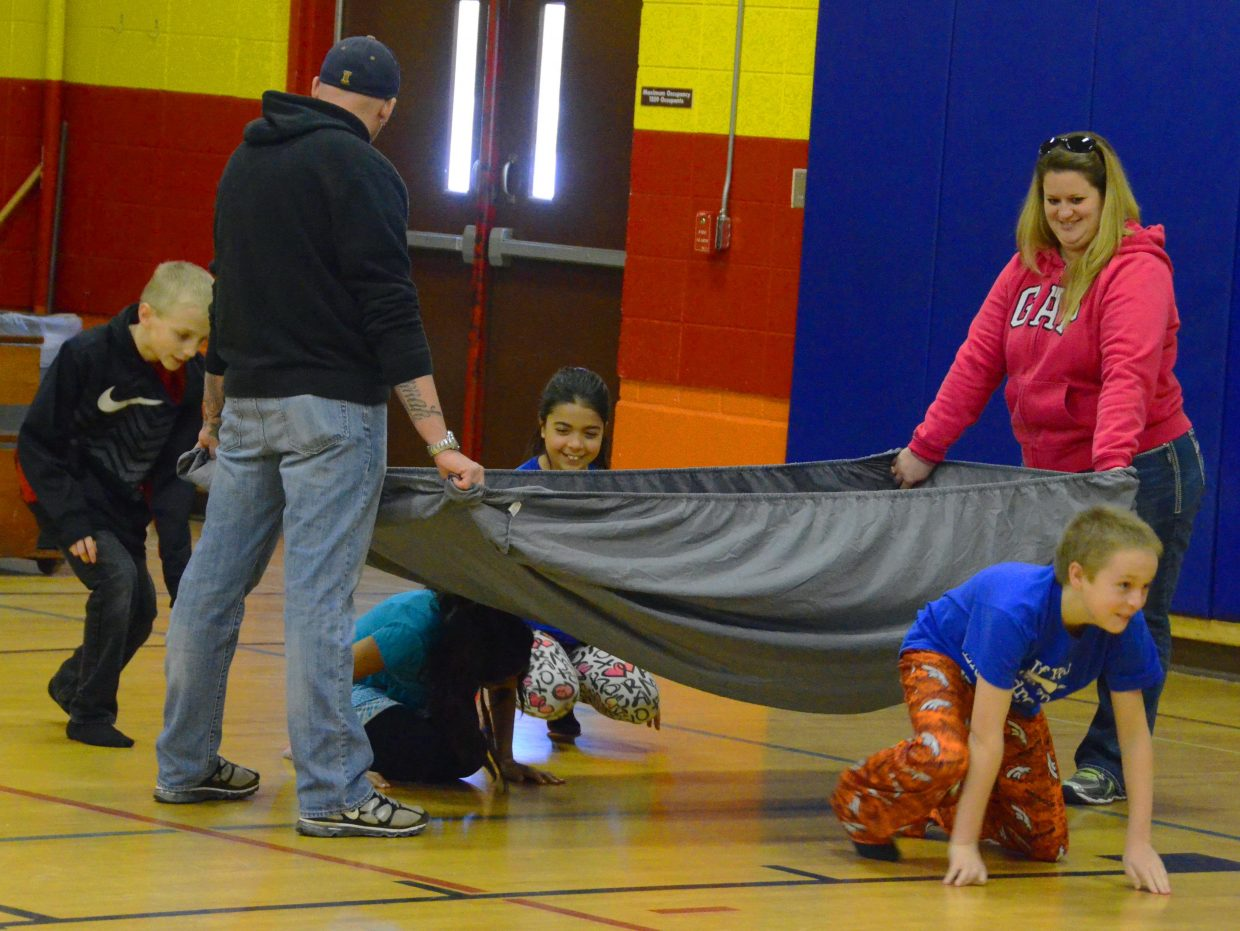 Sandrock Elementary School students crawl beneath a mock cloud of smoke during the firefighter obstacle course Friday afternoon in the school's gym. Students were able to interact with local firefighters during the activity, which included using real gear, rescuing stuffed animals and running through a series of hula hoops.