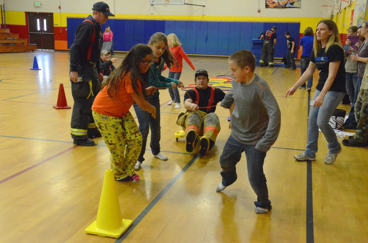 Craig Fire/Rescue's Jesse Doolin is pulled through a series of cones by Sandrock Elementary School students  during the firefighter obstacle course Friday afternoon in the school's gym. Six local firefighters, as well as Principal Kamisha Siminoe, were on hand working with students as they had fun during the activity.