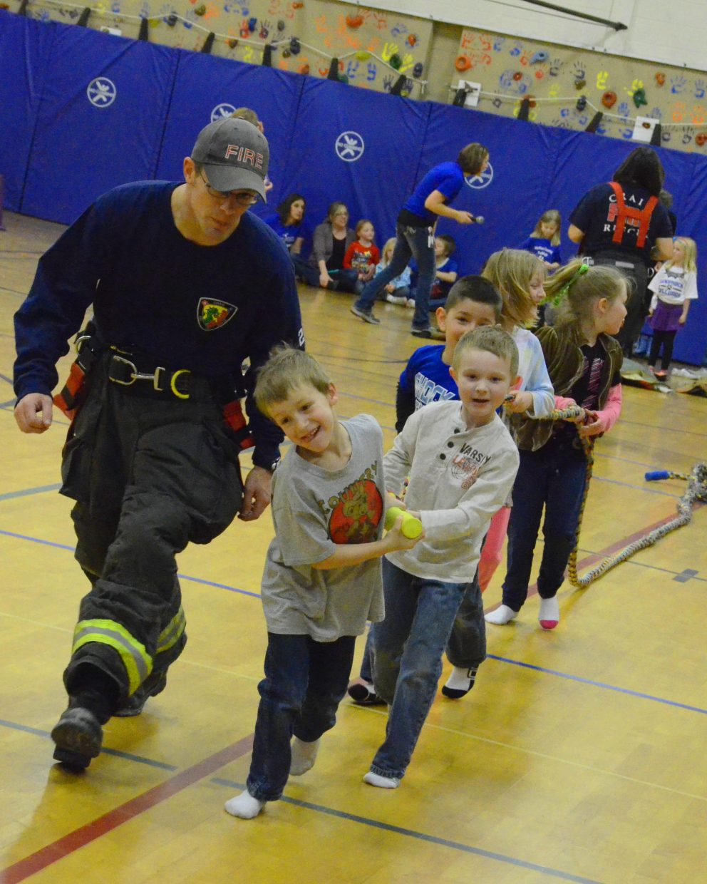 Craig Fire/Rescue's Ryan Hampton instructs Sandrock Elementary School students on how to run a fire hose during the firefighter obstacle course Friday afternoon in the school's gym. A lengthy rope replaced an actual hose in the drill, which more than 120 Sandrock kids got to do after helping raise $8,500 in the school's fall fundraiser.