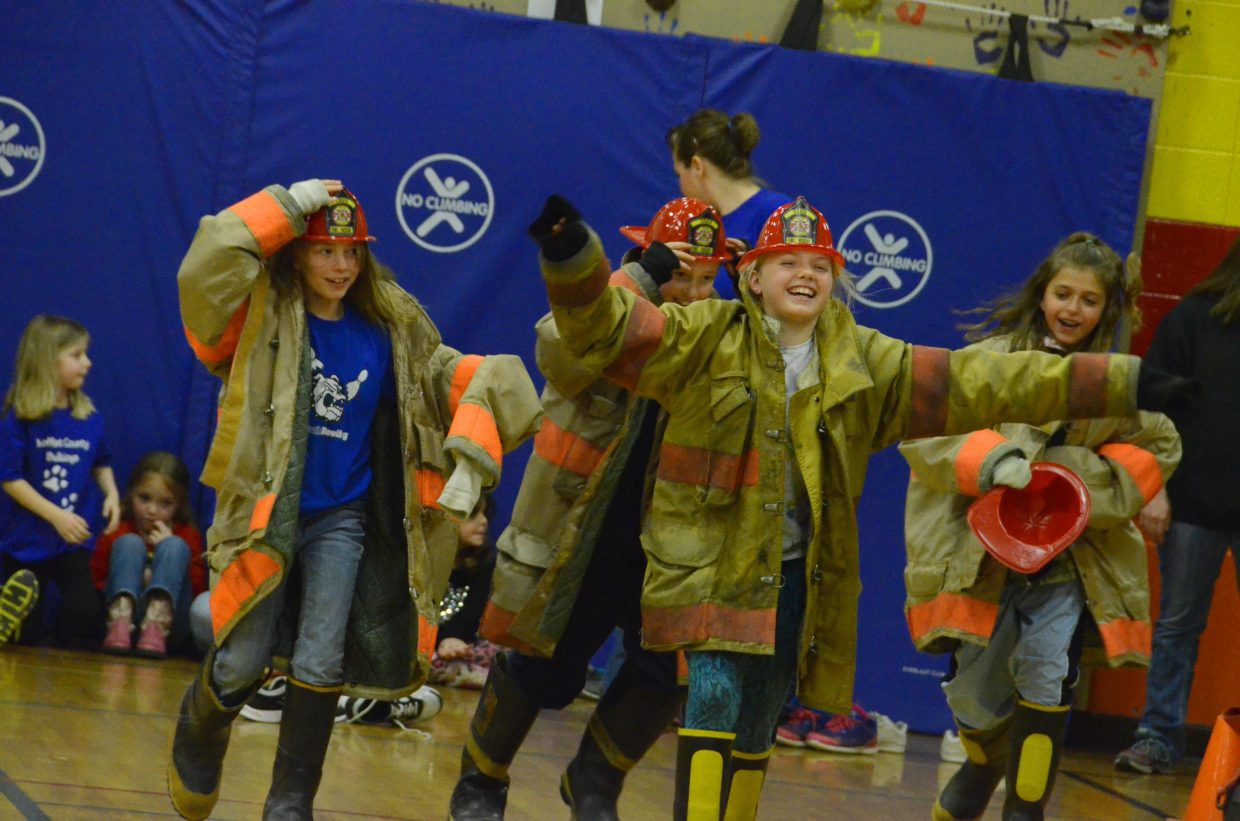 Sandrock Elementary School students suit up with real equipment provided by Craig Fire/Rescue during the firefighter obstacle course Friday afternoon in the school's gym.