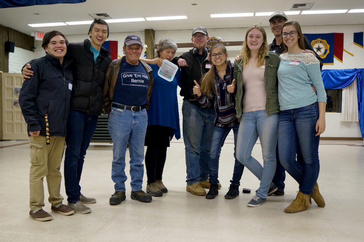 Bernie Sanders supporters Jake Steward, Travis Johnson, Bob Mannion, JoAnn Baker Paul, Andrew Jennings, Stephanie Duarte, Olivia Neece, Pearl Wyman and David Wyman pose for a photo after their candidate of choice won the presidential preference poll at the Moffat County Democratic caucus.