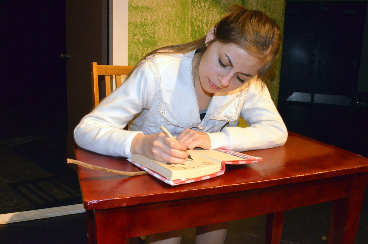 """Anne Frank (Stephanie Duarte) puts pen to paper while in hiding in """"The Diary of Anne Frank."""" The production about a group of Jewish people during the Holocaust is the spring play for Moffat County High School's theater department."""