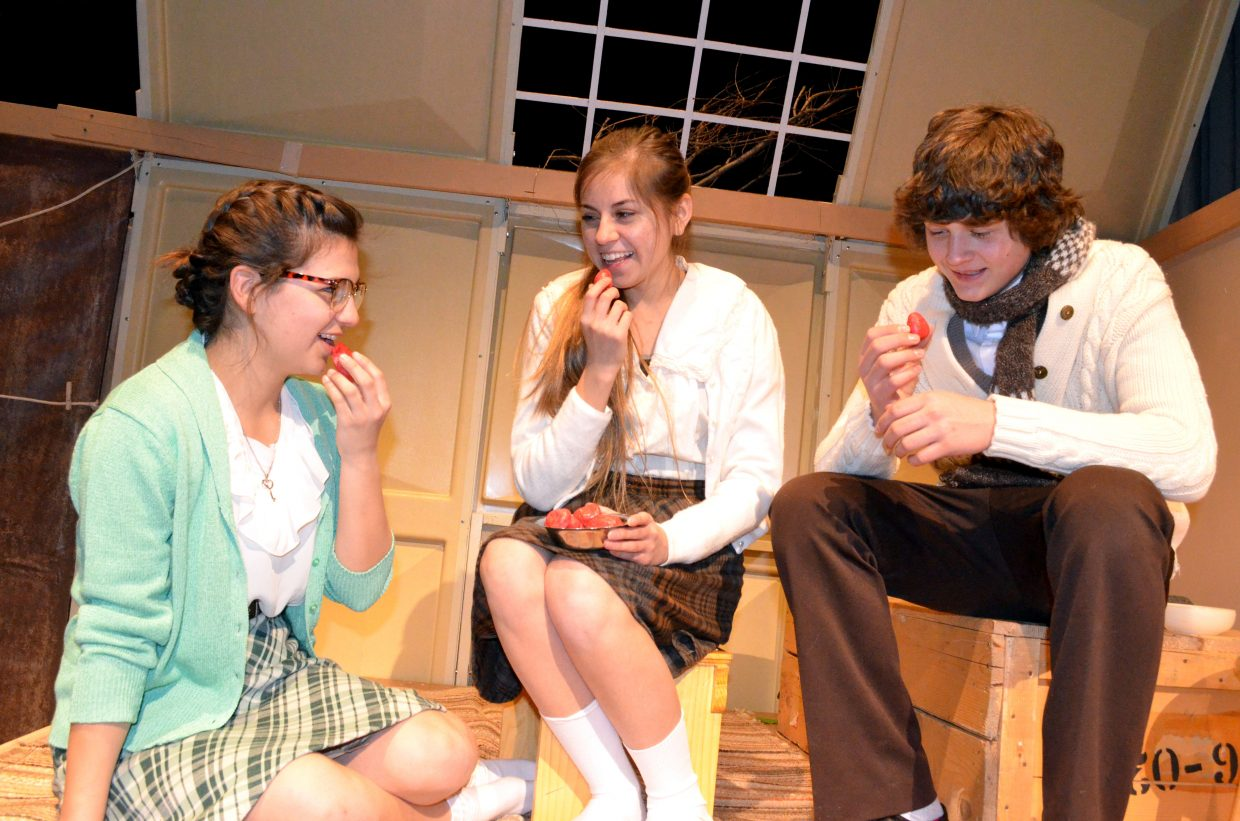 """From left, sisters Margot and Anne Frank (Bekah Bird, Stephanie Duarte) and (Peter Van Daan) Dylan Kernen enjoy a rare treat of strawberries while in hiding in """"The Diary of Anne Frank."""""""