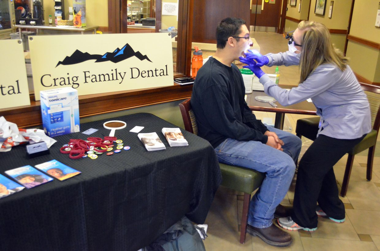 Crickett DeWall, of Craig Family Dental, provides an oral check-up for Andres Arredondo during The Memorial Hospital's annual health fair Saturday.