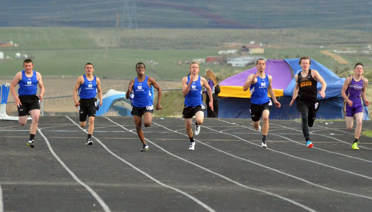 From left, Moffat County High School sprinters Elias Peroulis, Victor Silva, Gary Warrior, Kaden Hafey and Shandon Hadley tear down the track during the boys 200-meter dash Friday at the Clint Wells Invitational. Hadley won the race, one of 16 individual events in which MCHS took first place, the Bulldogs boys and girls teams also winning the overall meet.