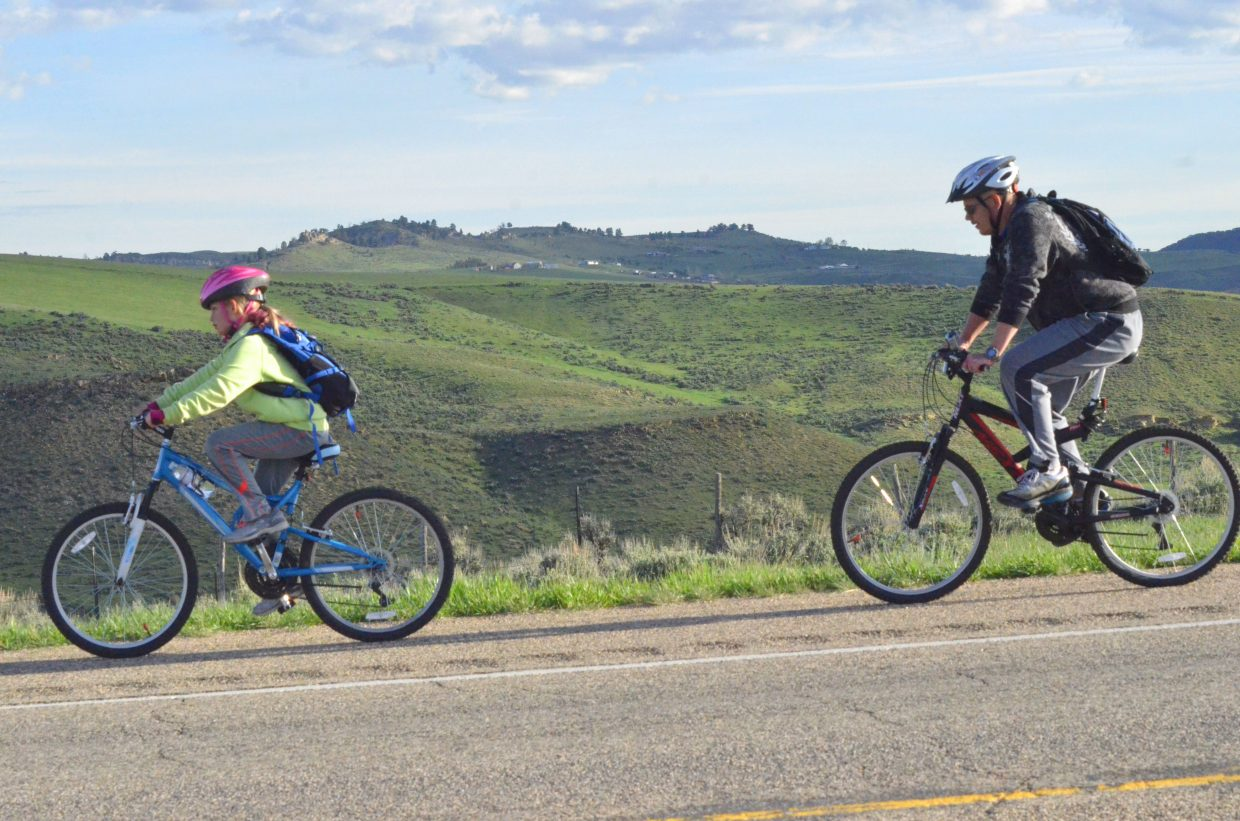 "Bicycle riders receive some relief and let gravity do the work after completing the incline along US Highway 40 during Saturday morning's ""Where the Hell's Maybell?"""