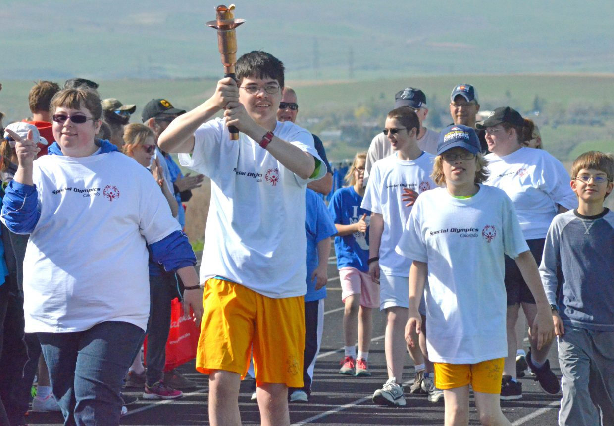 Craig athletes hold their heads high as well as the ceremonial torch to begin the Western Area Colorado Spring Special Olympic Games Saturday morning at Moffat County High School. The annual event featured competitors from across the Western Slope in track and field and aquatics.