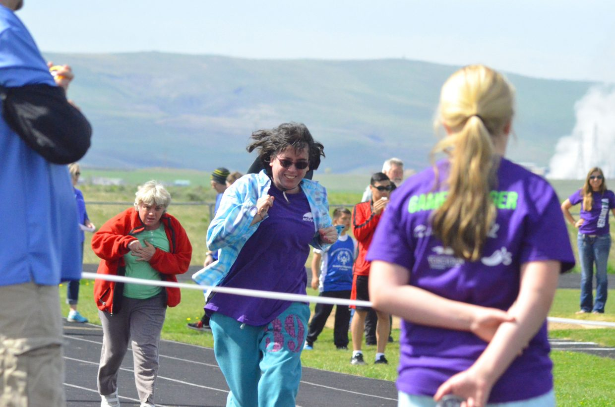 Competitors in the 50-meter dash near the finish line as volunteers cheer them on during the Western Area Colorado Spring Special Olympic Games Saturday morning at the Moffat County High School track.