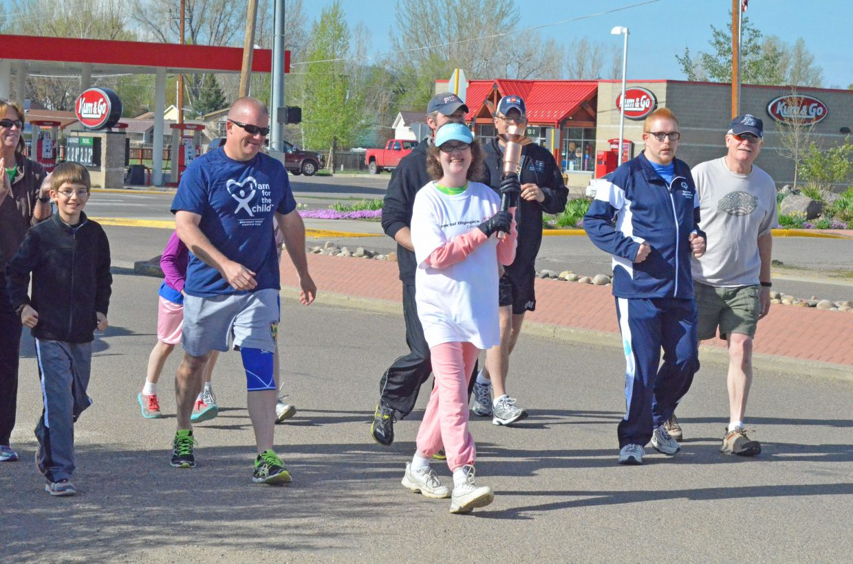 Craig athletes and volunteers kick off the Western Area Colorado Spring Special Olympic Games Saturday morning  by carrying the ceremonial along Finley Lane up to Moffat County High School.