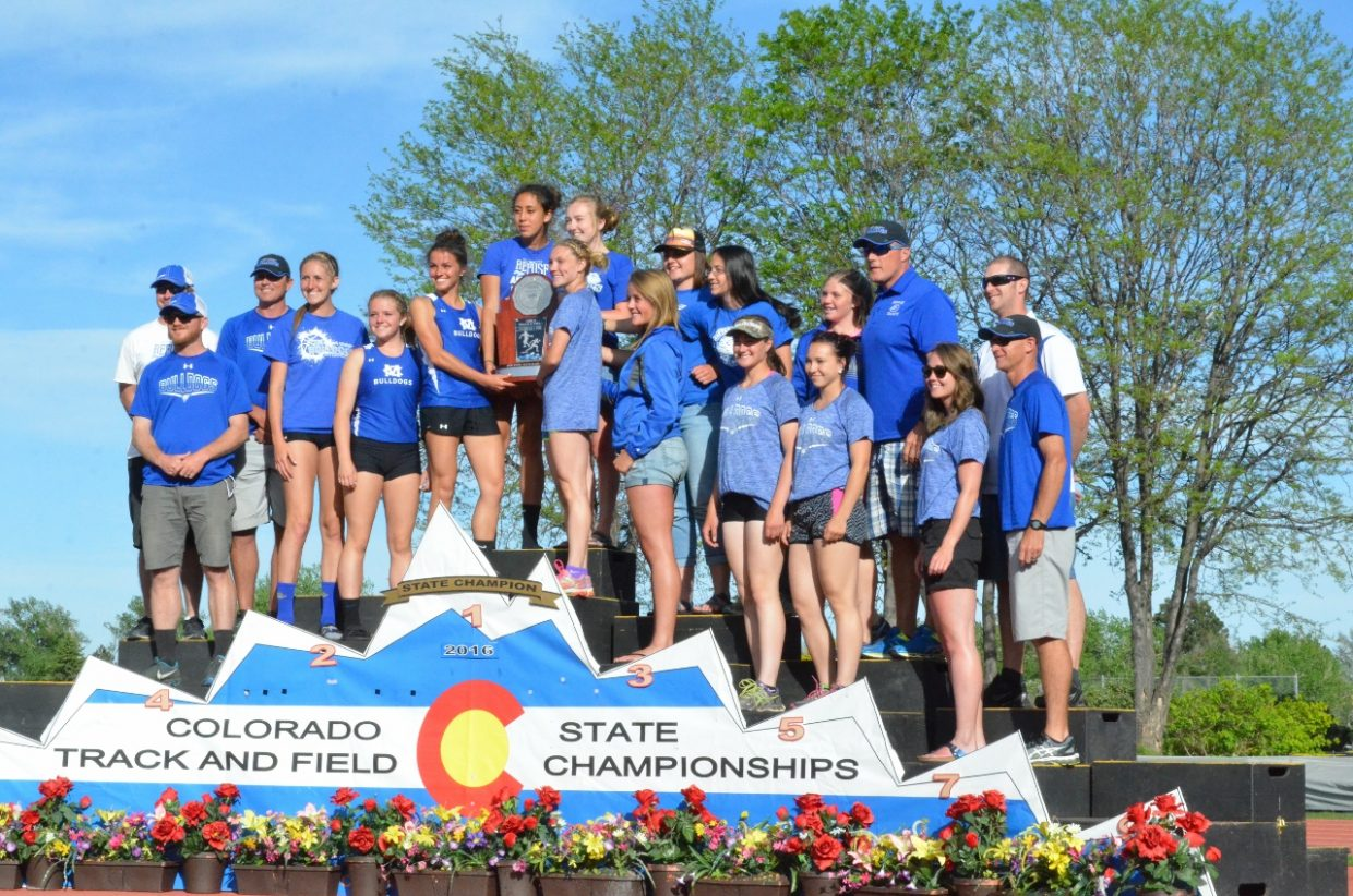 Athletes and coaches for the Moffat County High School girls track and field team stand atop the podium at the end of the State Championships, holding up a runner-up trophy after placing second overall in the 3A class. Bulldog girls won the 100-, 200- and 400-meter dash, as well as the 4x100 relay and placed in numerous other events.