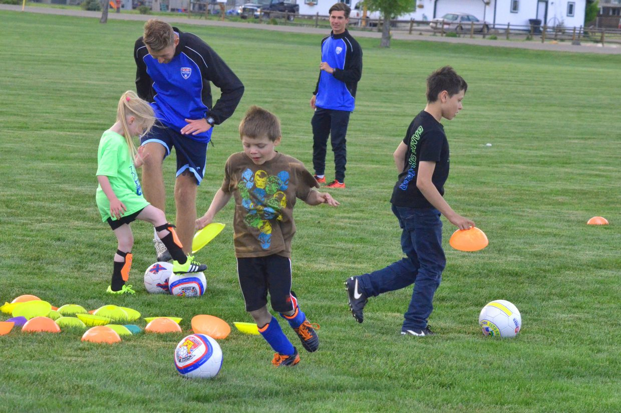 Young soccer players tackle a drill during a free skills clinic Tuesday at Woodbury Sports Complex as part of Challenger Sports British Soccer Camp. The full camp will be take place in Craig starting in late June.