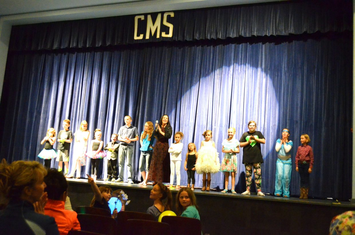 """The audience applauds enthusiastically for the members of Studio BV's vocal performance recital, """"Light Up the Stage"""" in the Craig Middle School auditorium, with the finale led by Bella Vocé director Jeana Womble, center. Womble taught numerous young singers and helped them coordinate individual acts as part of the show, which she puts on twice per year."""