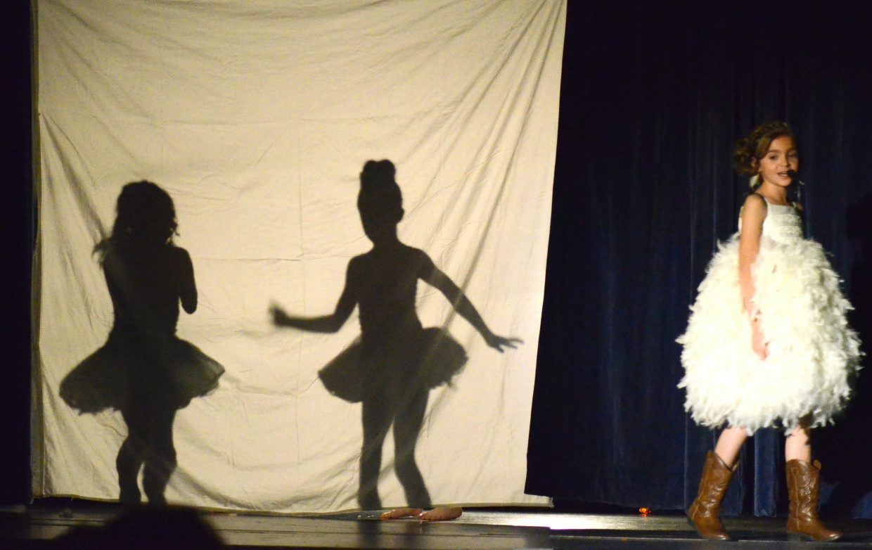 """Jordyn Mannon, far right, provides the lyrics of """"God Made Girls"""" while friends Heidi Snow and Haleigh-Ann Klein provide dancing silhouettes as part of Studio BV's vocal performance recital, """"Light Up the Stage"""" in the Craig Middle School auditorium."""