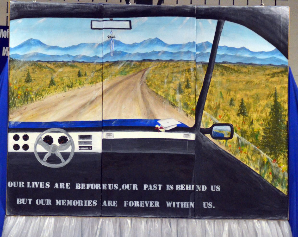 """The Moffat County High School Class of 2016 artwork features an automobile's windshield, open road and the quote, """"Our lives are before, our past is behind us, but all our memories are forever within us."""""""
