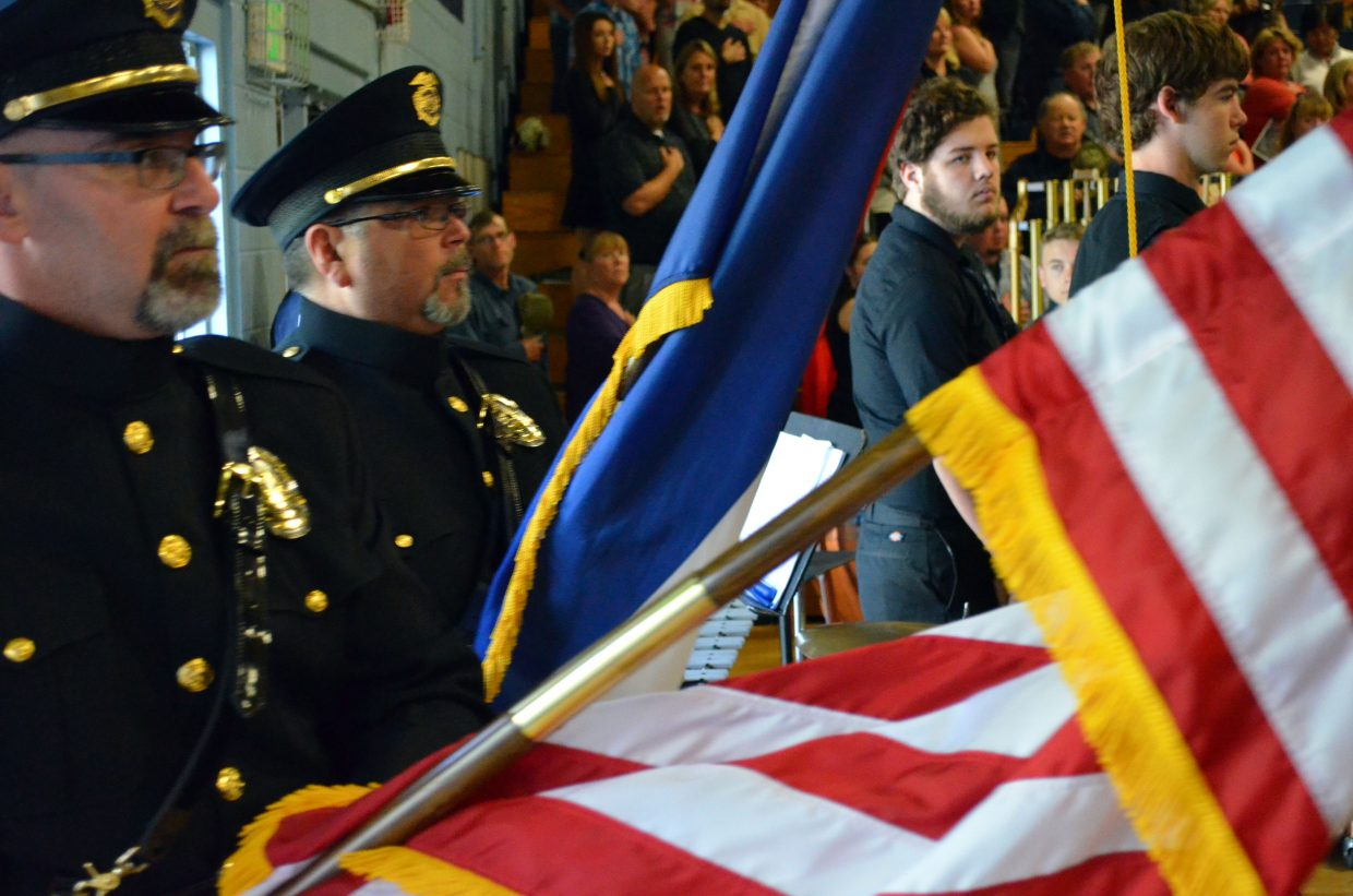 Audience members stand at attention as the Moffat County Honor Guard enters with the American and Colorado flags.