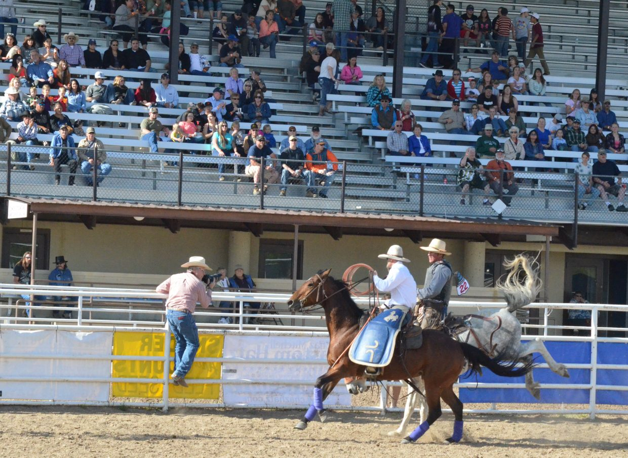 Spectators cheer on the contestants of the Iron Man Ranch Bronc Riding competitions at Moffat County Fairgrounds as part of Grand Olde West Days.