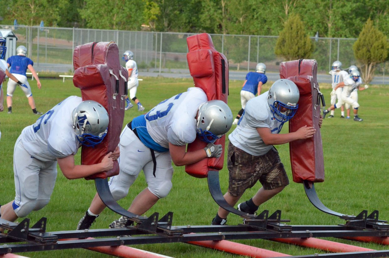 Members of the Moffat County High School football program hit the blocking sled during an evening session of the Bulldogs' skills camp on the MCHS practice field.