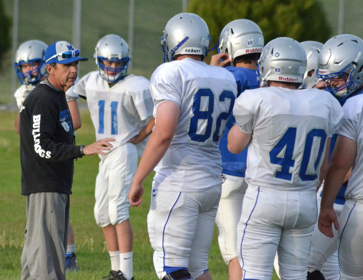 Moffat County High School coach Keith Gille guides players during the Bulldogs' skills camp on the MCHS practice field.