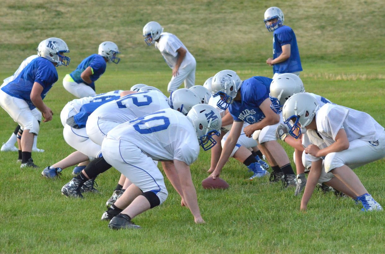 Moffat County High School football players get into position as they run through plays as part of Bulldogs' skills camp on the MCHS practice field.