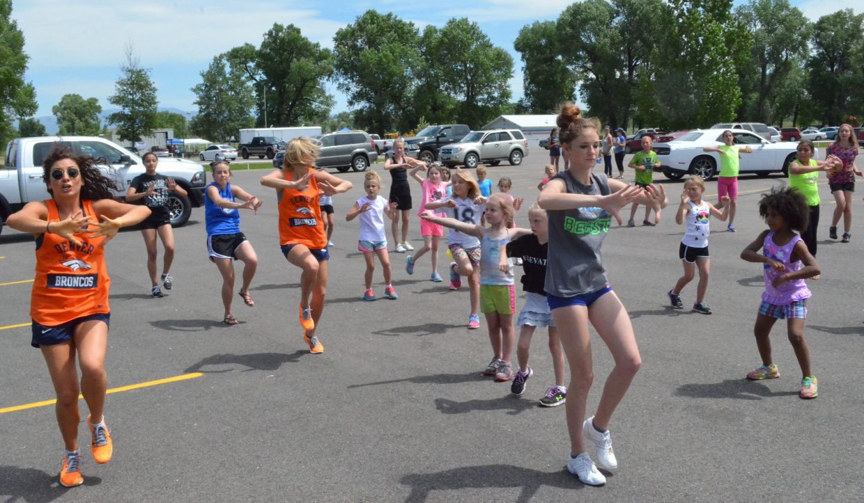 Members of the Denver Broncos cheerleaders work with Craig girls on a routine Saturday at Loudy-Simpson Park as part of the Victory Motors Cancer Drive. Cheerleaders and football players in attendance also provided autographs.