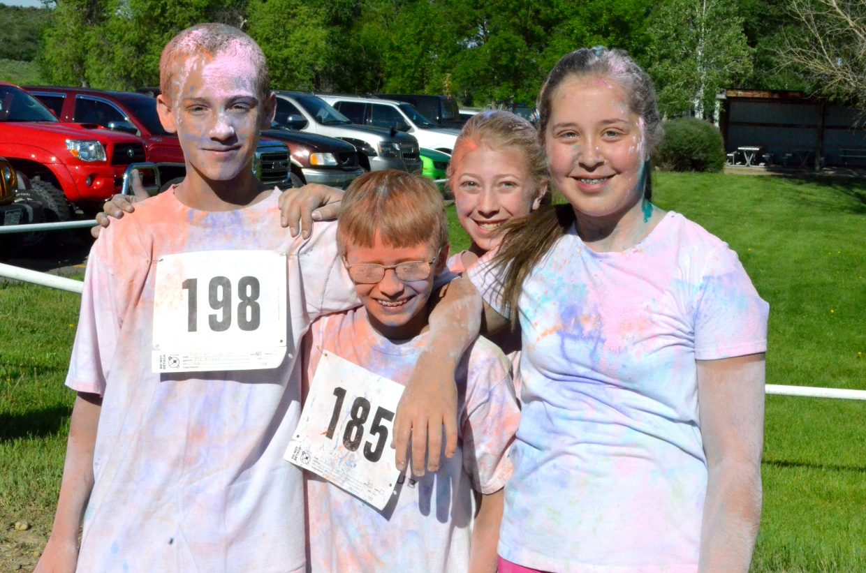 """From left, young runners Brock Hartung, Eric Doolin, Mackenzie Schneider and Allison Jacobson catch their breath following the 5K Color Run/Walk Saturday at Loudy-Simpson Park as part of the Victory Motors Cancer Drive. Doolin claimed he was continually """"spitting pink"""" as a result of the many colors runners were hit with along the course."""