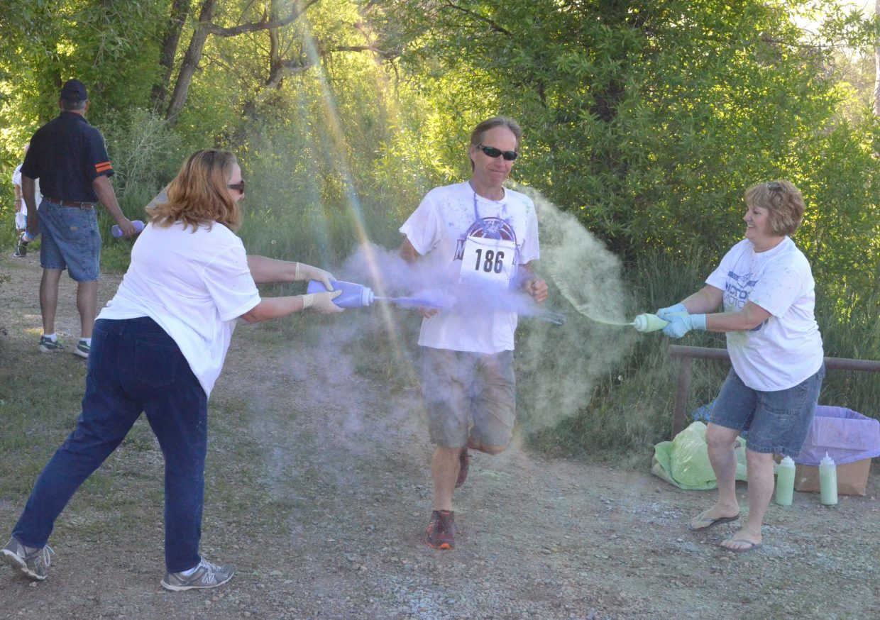 Volunteers cover runner Derek Cleverly with color as he exits the Nature Trail Saturday at Loudy-Simpson Park during the 5K Color Run/Walk as part of the Victory Motors Cancer Drive.
