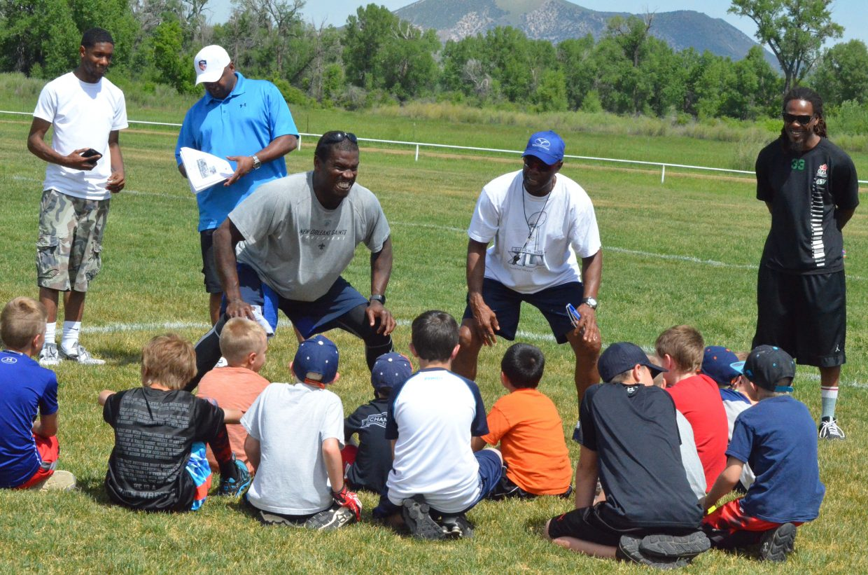 Former NFL stars Anthony Hargrove and Rick Upchurch show young athletes how to put on their game face during the NFL Play 60 Challenge Saturday at Loudy-Simpson Park as part of the Victory Motors Cancer Drive.