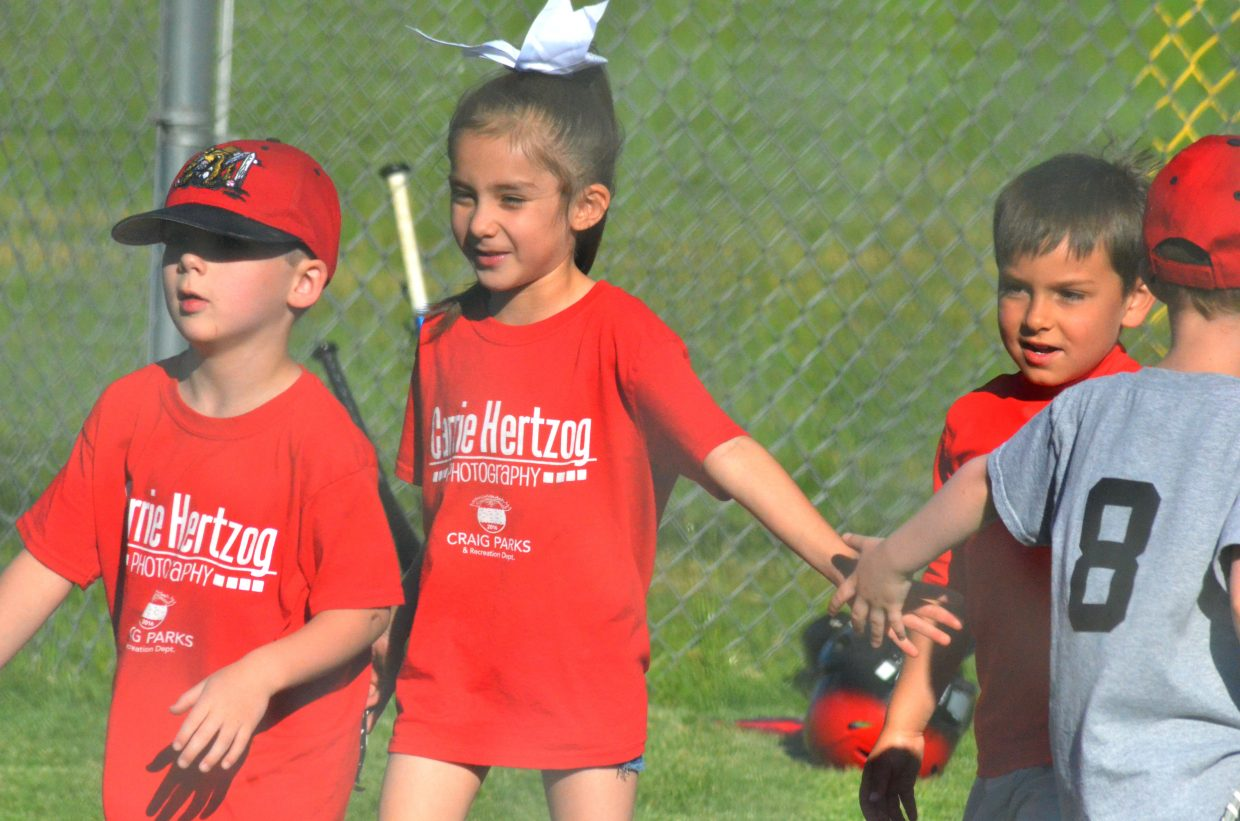 Members of Carrie Hertzog Photography exchange congratulations with the Craig Daily Press t-ball team following a Thursday night game at Woodbury Sports Complex.