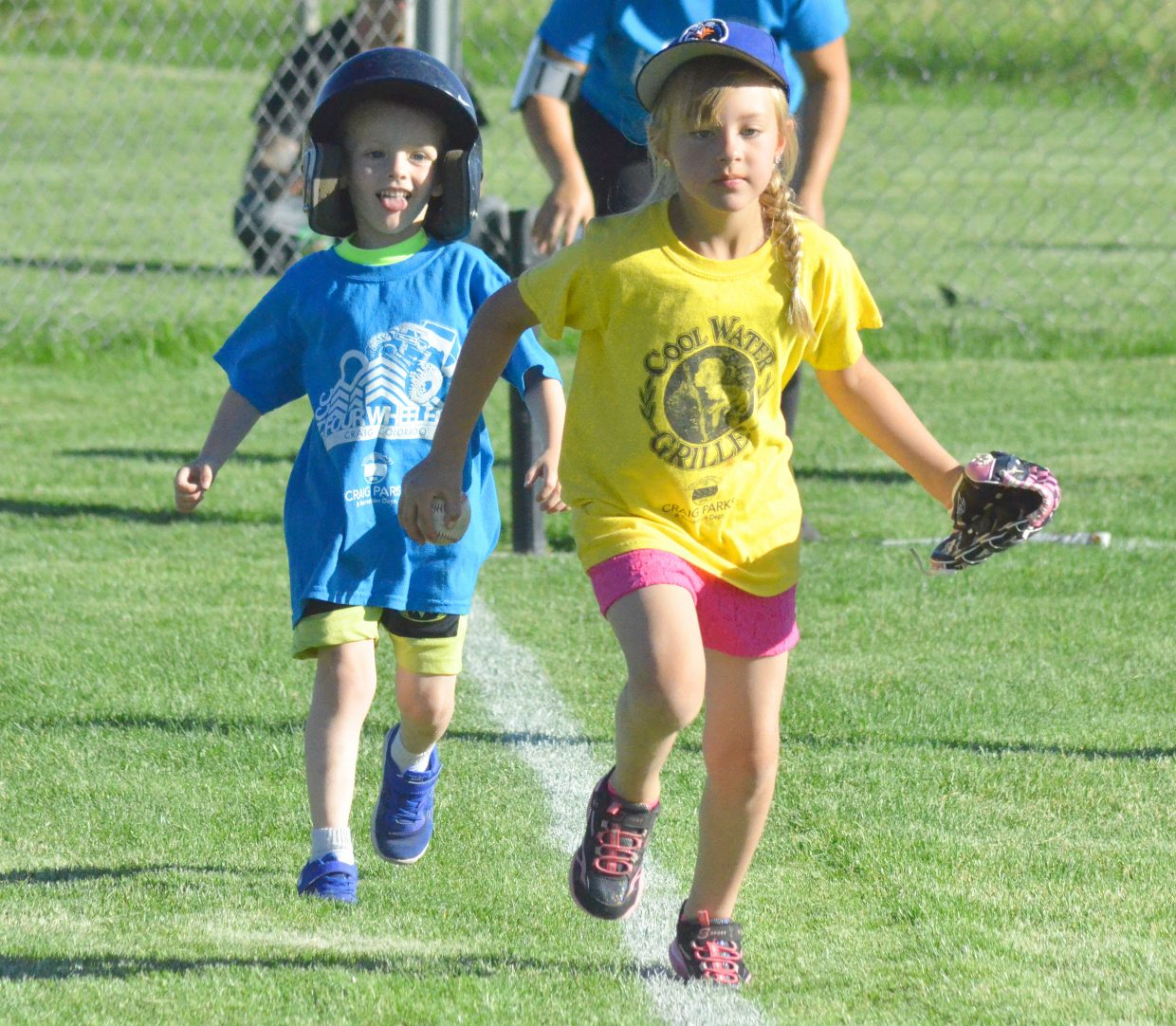 Baserunner Kael Higgins, of CNCC Four-Wheelers and fielder Kadynce Hampton, of Cool Water Grille, speed toward first base during a Thursday t-ball team at Woodbury Sports Complex.