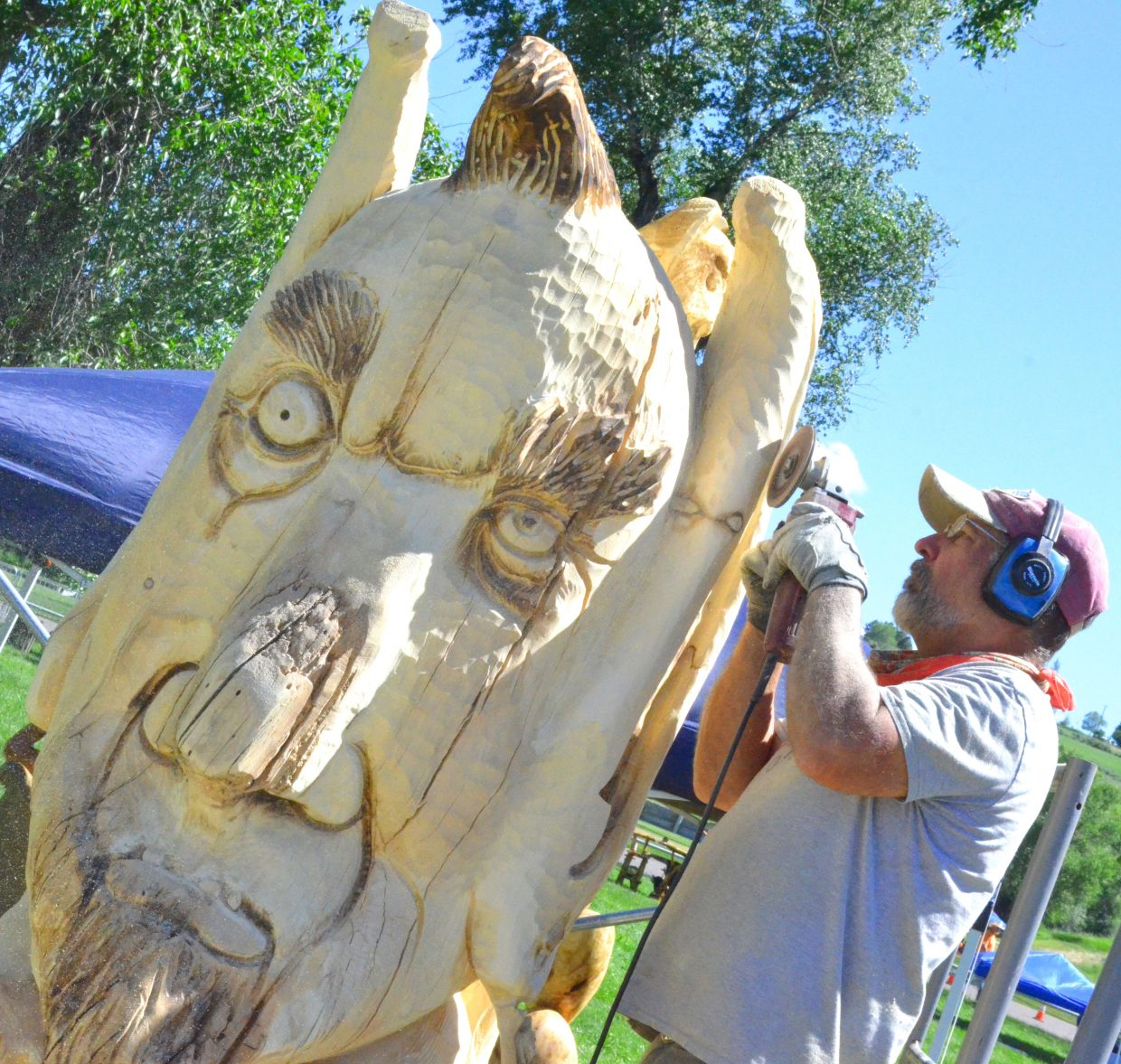 """Salt Lake City's David Mitchell focuses on the intricate details of """"The Magician"""" Friday as part of Whittle the Wood Rendezvous. The 11 carvers will finish their works Saturday afternoon, with prizes being given out later in the day."""