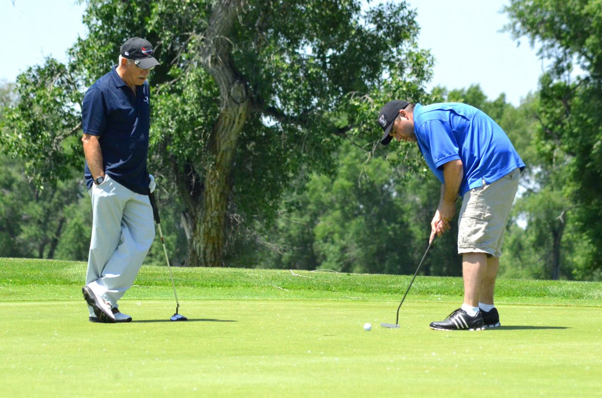 RC Buckley, left, observes as Travis Sondrol takes a short putt on the 12th green of Yampa Valley Golf Course Friday during the first day of the 49th annual Cottonwood Classic. Bits of cotton were scattered through the air and on the greens and fairways during YVGC's yearly tournament, with 97 golfers attending this year.