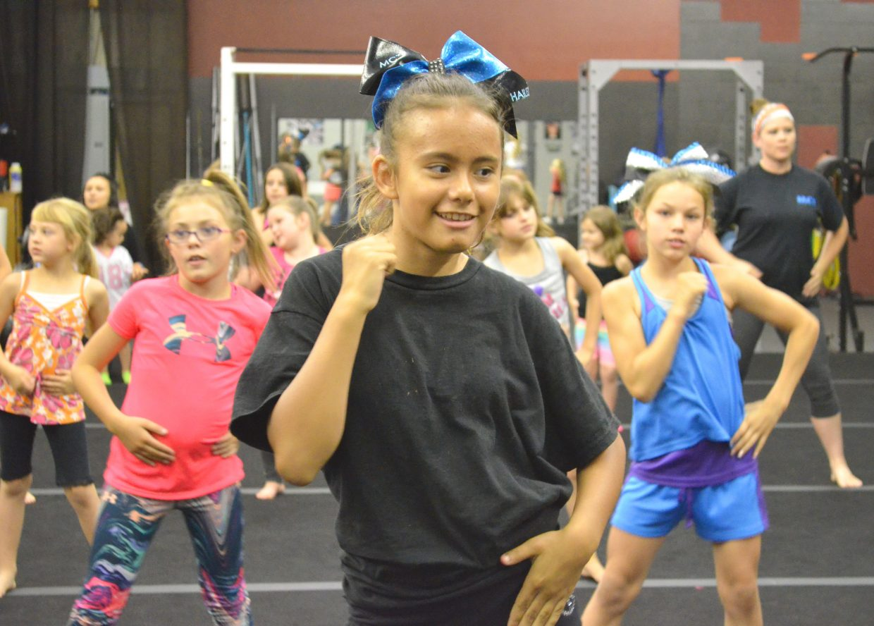 Moffat County Thunder Cheer's Hailey Collins and teammates work on the dance routine they will perform during the Fourth of July parade in downtown Craig.