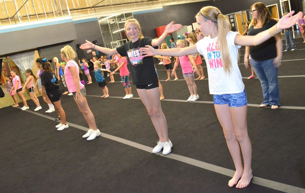 Participants in the Moffat County Thunder Cheer clinic get their hands in the air prepping for a performance that will take place during the Fourth of July parade.
