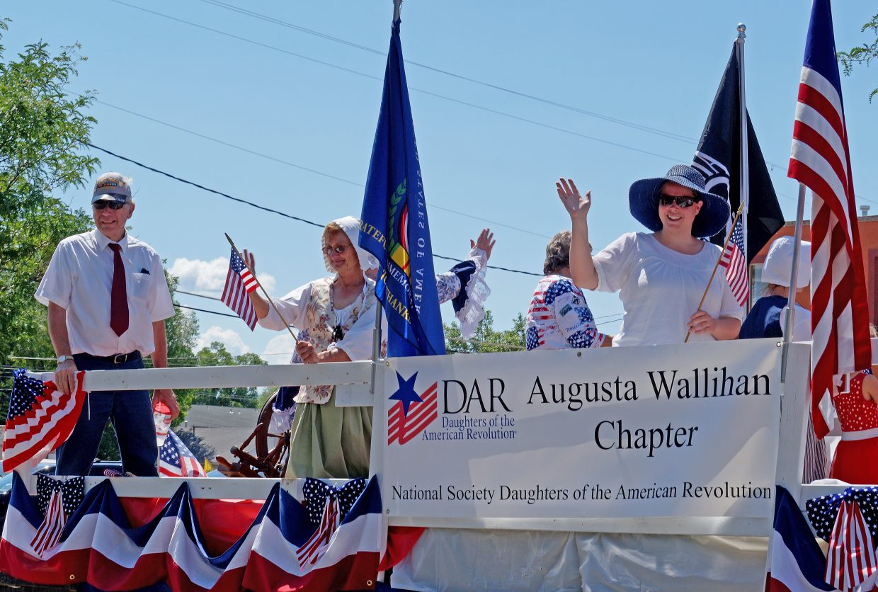 The local Daughter's of the American Revolution Chapter, dressed in period clothing, waves to the crowd.