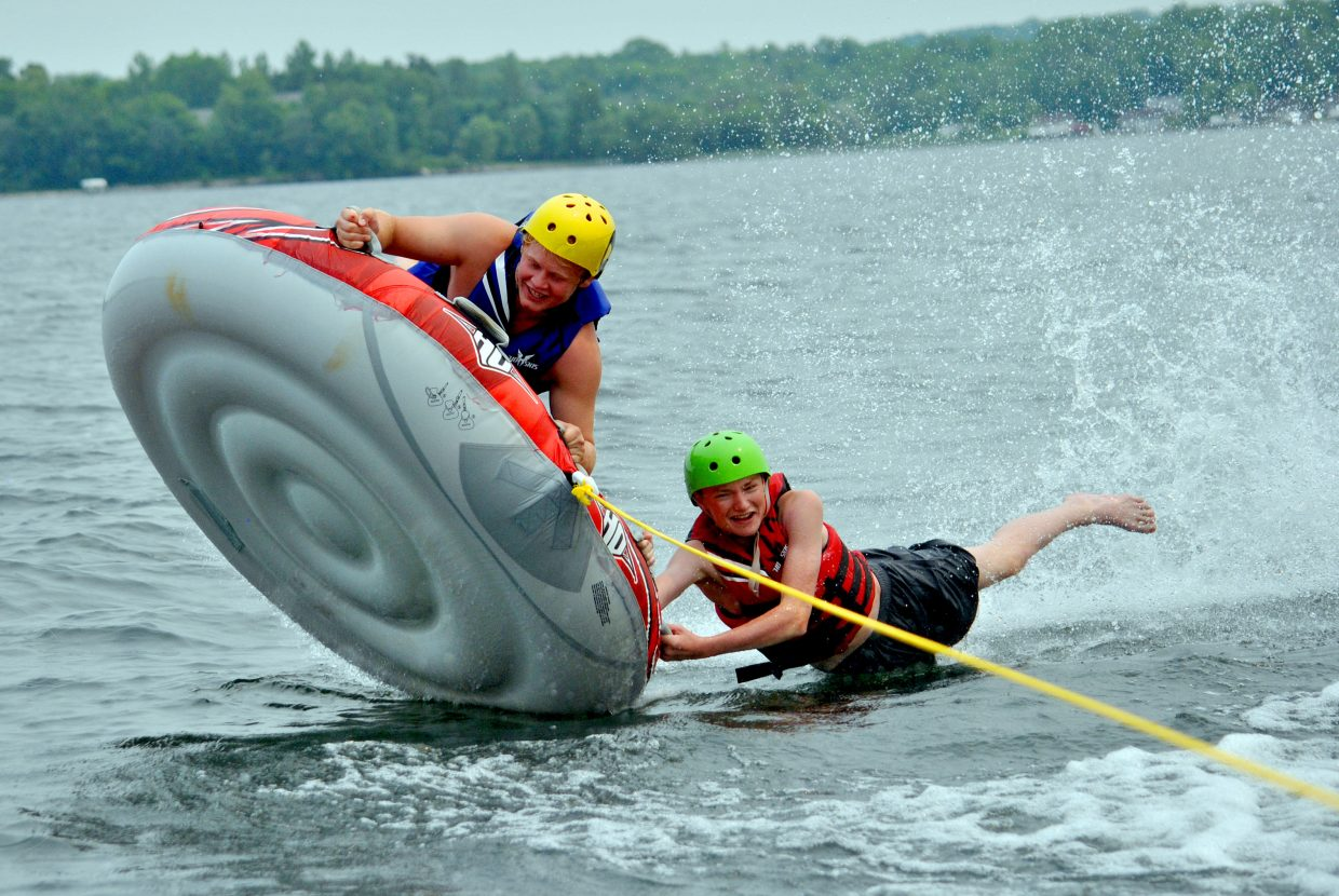 Lane White, right, holds on with one arm while Christian Carson commandeers a tube on Pelican Lake at Castaway Club Young Life Camp.