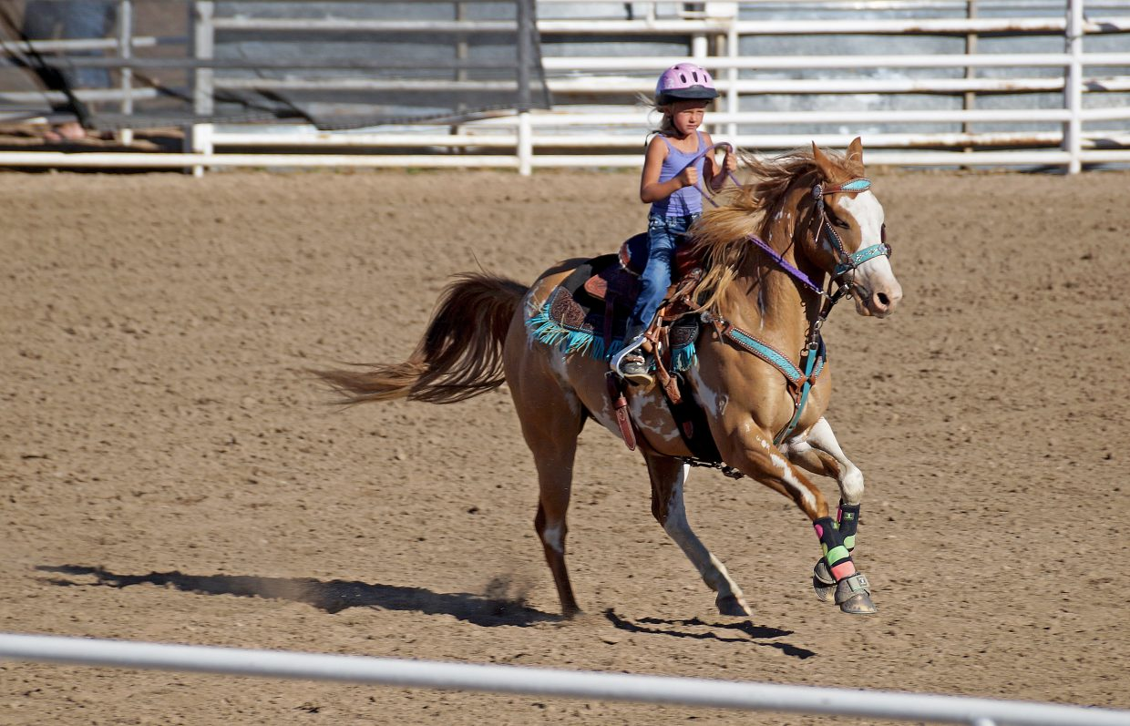 Alexis Vreeman rushes out of the gate at the start of a barrel race.