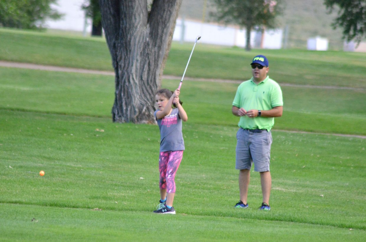 Haley Bri Duran, 7, chips away along the seventh fairway of Yampa Valley Golf Course as dad Ryan stands back and observes as part of the PGA Junior Golf Academy Tuesday at YVGC.