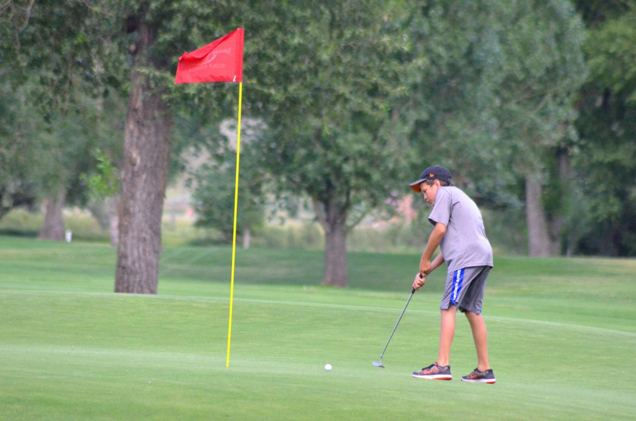 Isaac Vallem, 11, sinks a putt on the seventh green of Yampa Valley Golf Course.