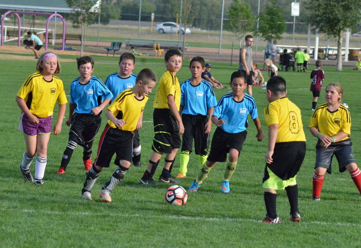 The blue and yellow teams get back into motion following a blue goal during a Tuesday game of the Craig Parks & Recreation Youth Soccer's 10U league at Woodbury Sports Complex.