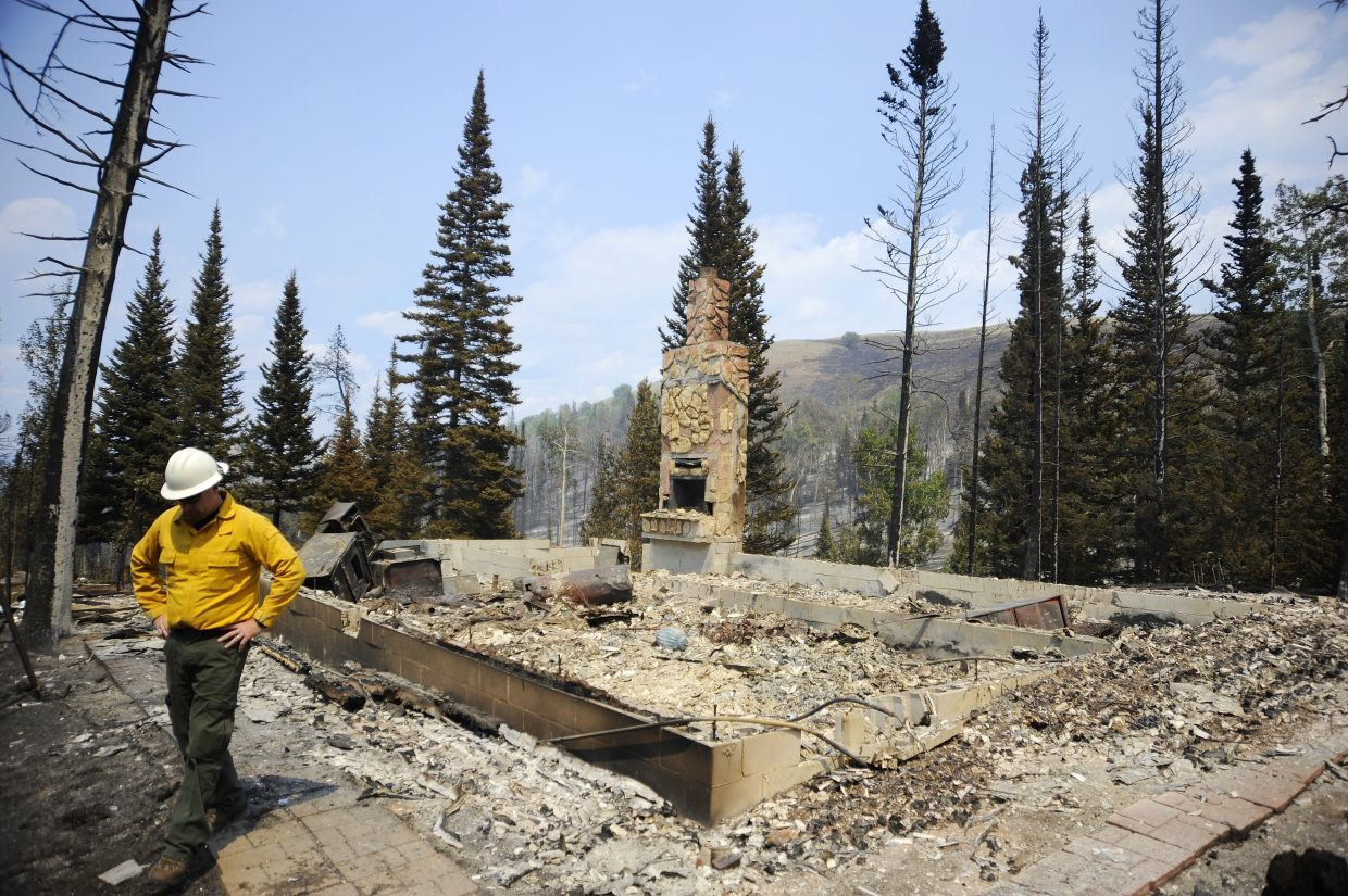 Steamboat Springs U.S. Forest Service District Ranger Chad Stewart on Friday walks away from the ruins of a cabin that was destroyed Wednesday in the Beaver Creek fire in Jackson County. The cabin was the most significant loss at the fire so far.