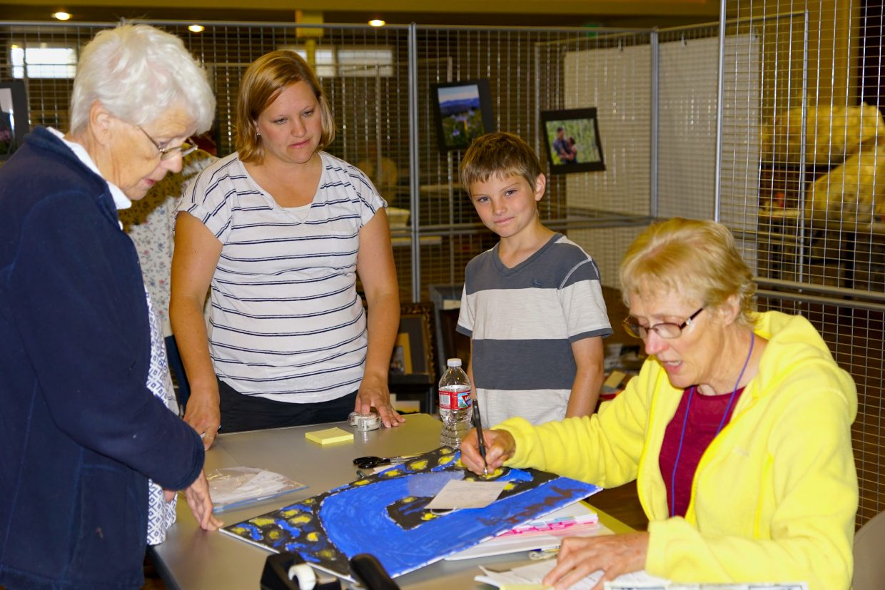 Jonah Jenison enters artwork in the 2016 Moffat County Fair with the assistance with his mother Courtney Jenison and long-time fair volunteers Jane Hume and Donna Sweet.