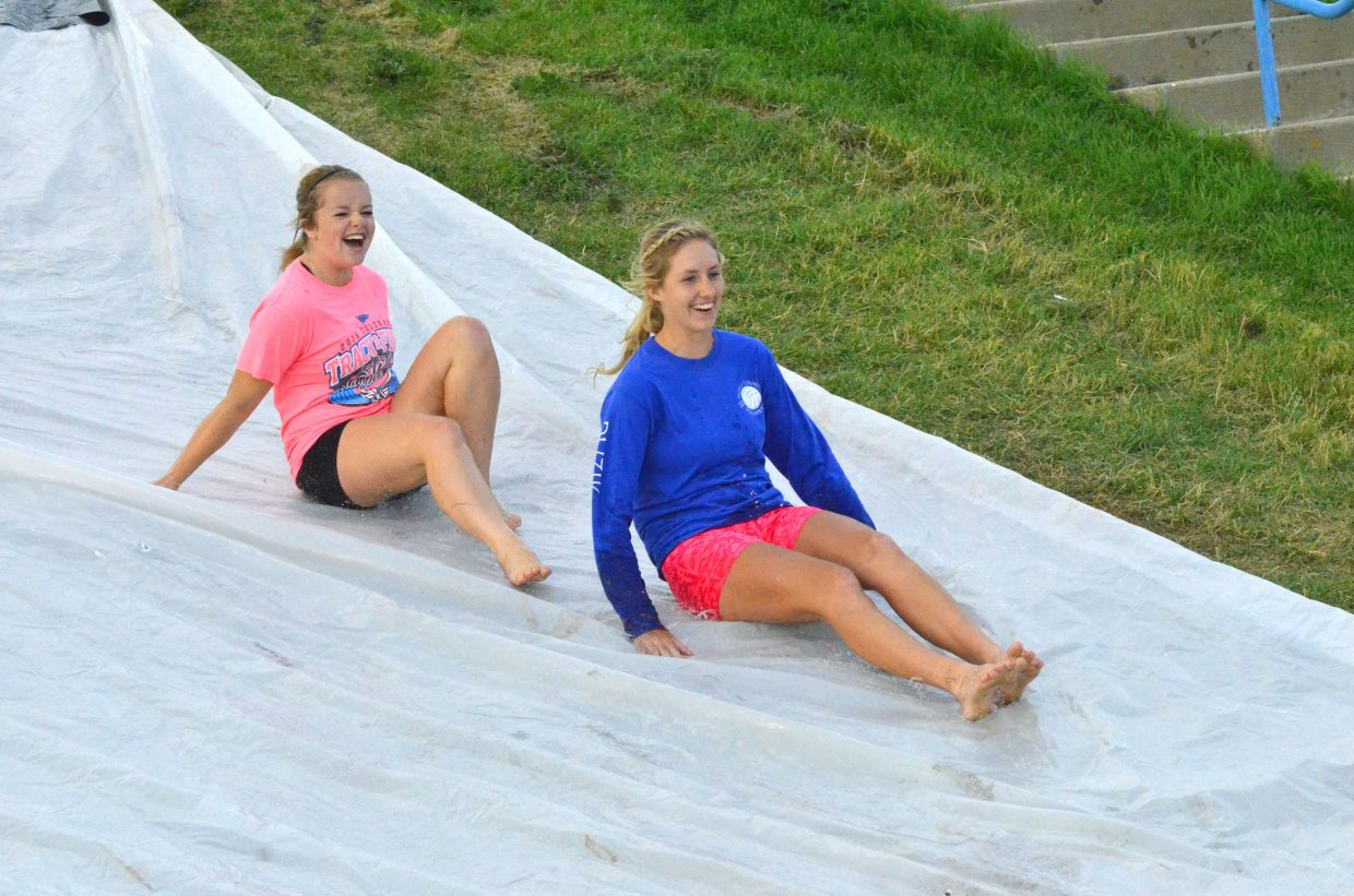 Emma Samuelson, left, and Mattie Jo Duzik zip down the Slip 'N Slide on the Moffat County High School hill, hosted Wednesday by Grand Futures Prevention Coalition and Moffat County Teen Council.