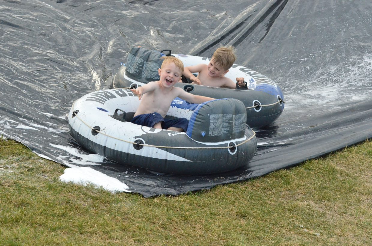 Brothers Jonas and Ryun Pressgrove laugh as their inner tubes collide along the Slip 'N Slide hosted Wednesday at Moffat County High School by Grand Futures Prevention Coalition and Moffat County Teen Council.