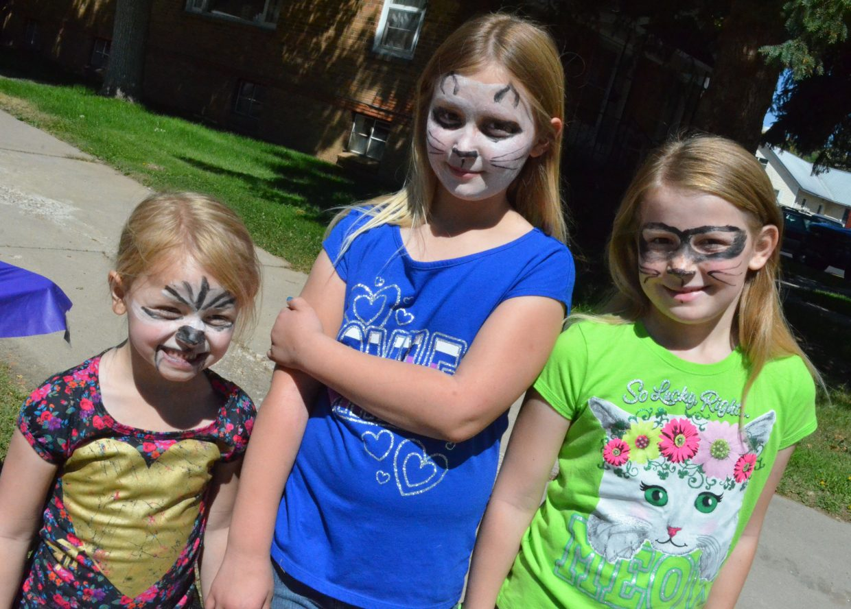 Sisters Nellie, 5, Catherine, 9, and Lillian Clark, 8, display the new animal faces for the day, as painted on by members of Calvary Baptist Church during Saturday's Back-to-School Fair, hosted by Love INC of the Yampa Valley. at Breeze Street Park.