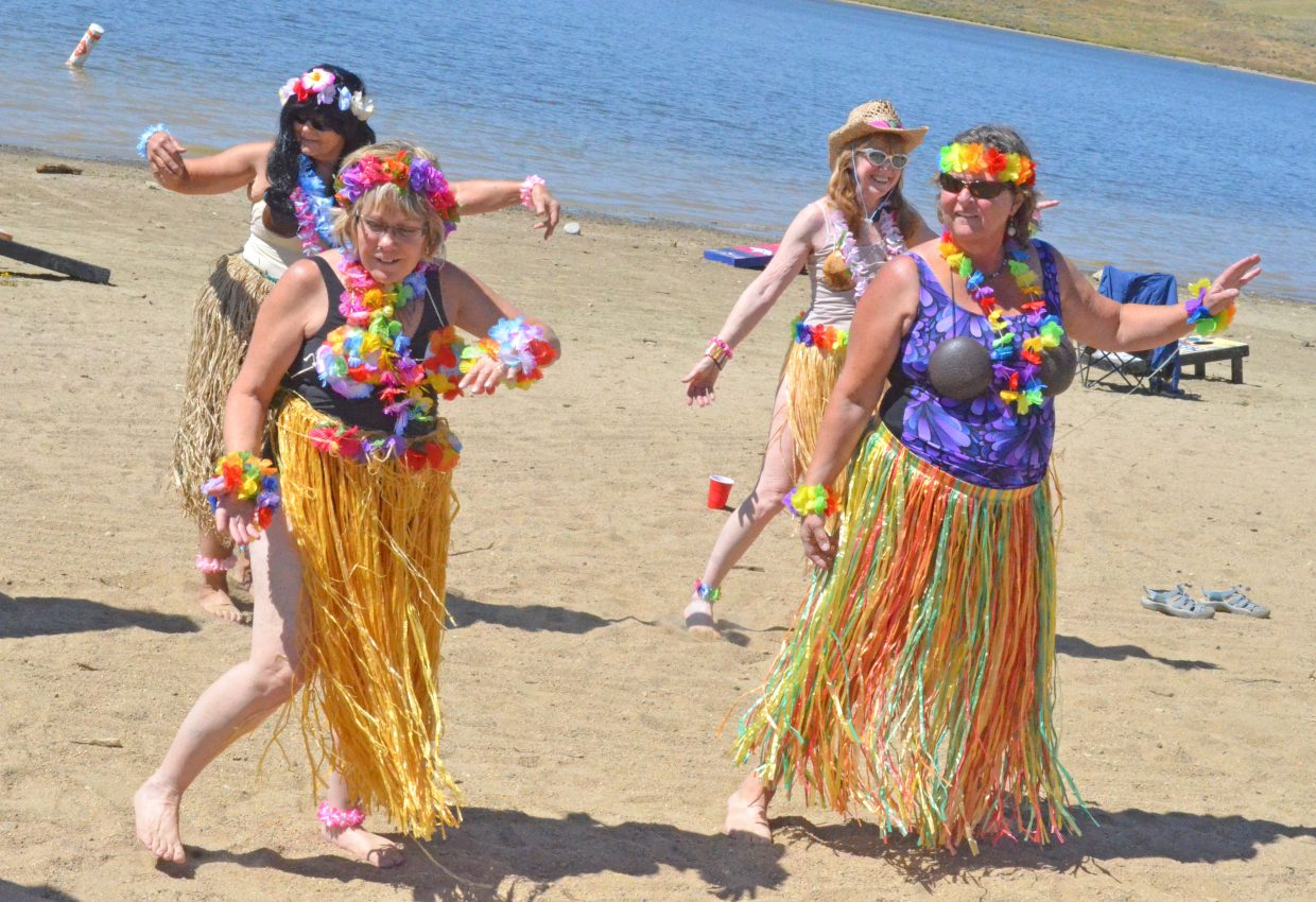 From left, Marilyn Rieser, Lynn Barclay, Janele Husband and Dory Brown display the traditional dance routine of the Northwest Colorado Chapter of Parrotheads during the group's Luau at the Lake Saturday at Elkhead Reservoir. The troupe was also joined by Julie Sperl and Katie Johnson.
