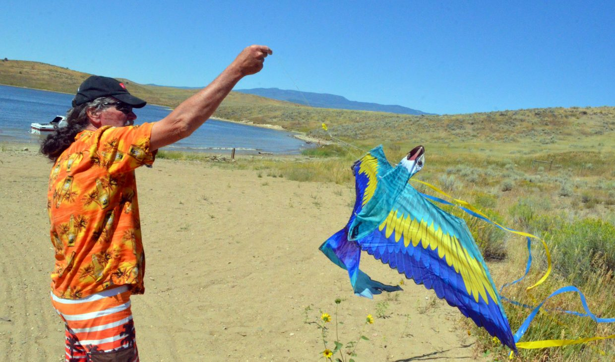 John Husband works to keep a parrot kite aloft during the Northwest Colorado Chapter of Parrotheads Luau at the Lake Saturday at Elkhead Reservoir.