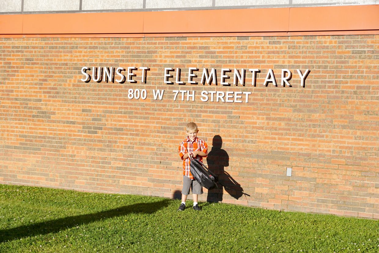 Children take turns standing under the Sunset Elementary School sign so that parents may take back to school photos for the start of the 2016-17 school year.