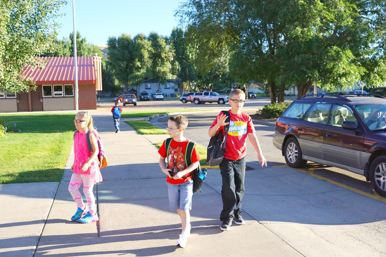 Second-grade student Anastasia Robertson, second-grade student Devon Bollman and fifth-grade student Zane Neal head to Sunset Elementary School for the first day of the 2016-17 school year.